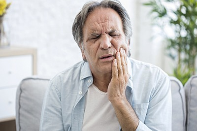 Man in pain needing an emergency dentist in Crown Point.