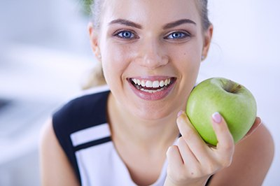 Woman with a healthy smile needing an apple.