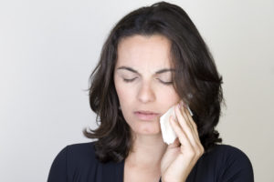Woman in pain holding compress to face
