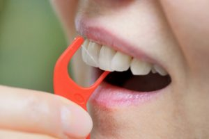 person using a floss pick