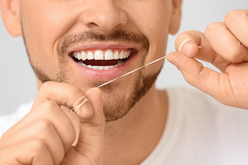loseup of man holding dental floss
