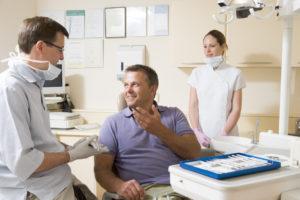 Dentist talking to man in dental chair
