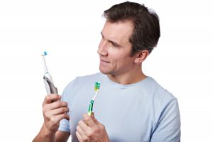 A man comparing an electric and manual toothbrush.